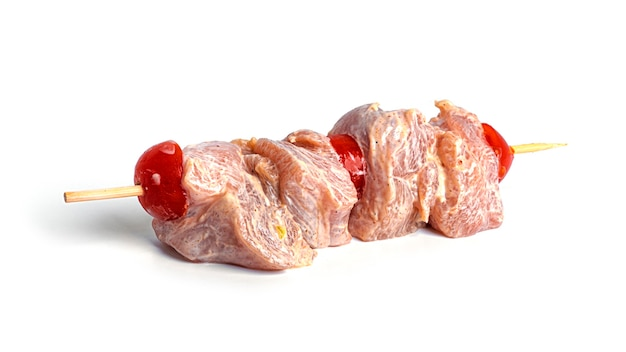 白地にチェリートマトを添えた生鶏の串焼き。スブラキが分離されました。