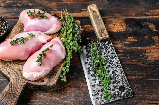 木のまな板に生の鶏皮なしもも肉。黒の背景。上面図。スペースをコピーします。