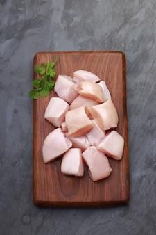껍질을 벗기지 않은 생 닭고기 부드러운 튀김은 나무 판자에 배열되고 고수 잎으로 장식됩니다.