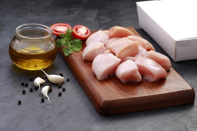 나무 판자에 껍질을 벗기지 않은 생 닭고기 부드러운 프라이 컷