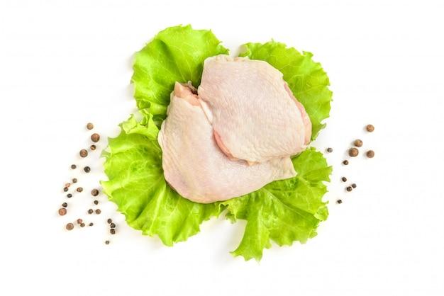 Сырые куриные бедра и зеленый салат, изолированные на белом фоне.