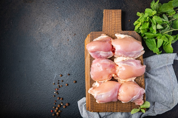 Raw chicken thigh boneless pulp meat poultry or turkey fresh ready to eat meal snack on the table