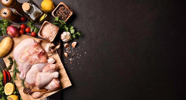 Сырые куриные бедра и куриные окорочка с ингредиентами для приготовления на черной каменной поверхности