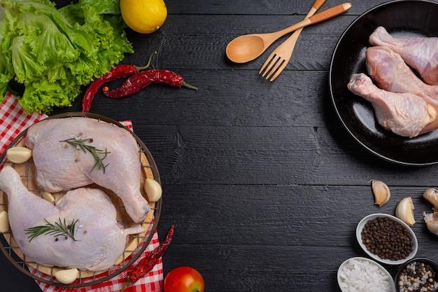 Cosce di pollo crude sulla superficie di legno scuro.