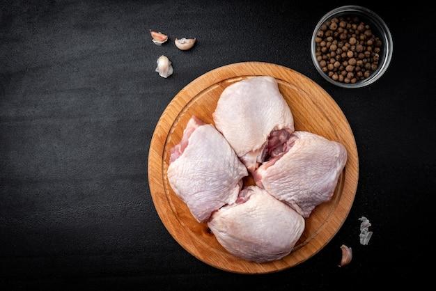 블랙 테이블에 원시 닭 허벅지입니다.