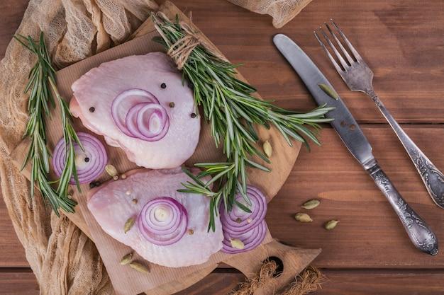 まな板にローズマリー、赤玉ねぎ、胡椒を添えた生の鶏の太もも。未調理の鶏肉。料理の材料。フラットレイ