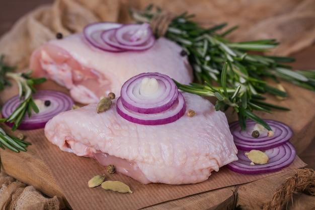 Сырые куриные бедра с розмарином, красным луком и перцем на разделочной доске. сырое мясо птицы. кулинарные ингредиенты для приготовления пищи
