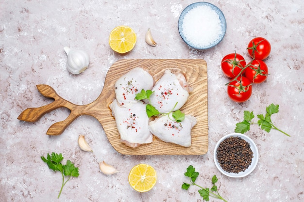 Raw chicken thighs with spices parsley on wooden cutting board,top view