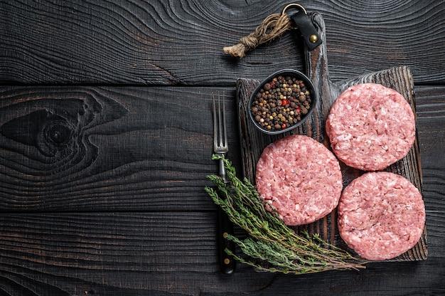 원시 치킨 칠면조 패티, 도마 보드에 갈은 고기 커틀릿. 검은 나무 테이블. 평면도.