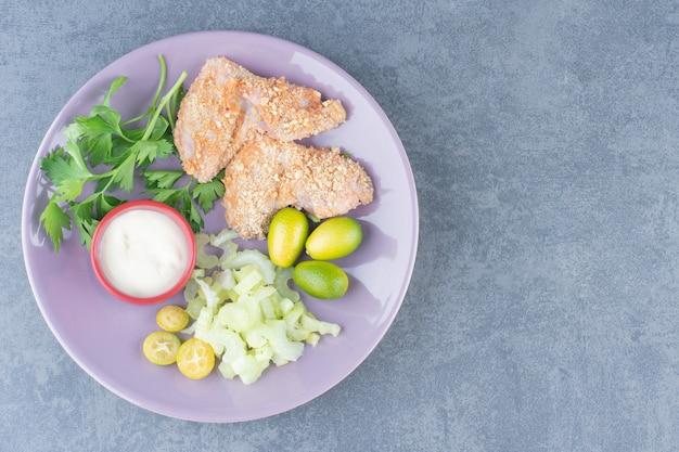 Сырые наггетсы куриного крыла на фиолетовой тарелке.