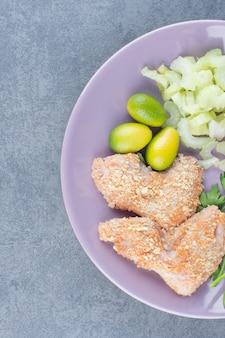 Pepite di ala di pollo crude sul piatto viola.