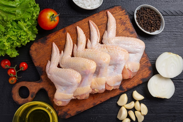 Raw chicken wings on the dark wooden surface.