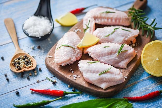 Сырые куриные крылышки, зелень и специи с перцем и лимоном для приготовления тайской азиатской кухни курица с розмарином