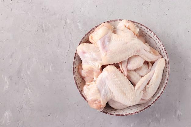 밝은 회색 배경, 상위 뷰, 가로 형식, 텍스트를위한 공간에 접시에 생 닭 날개