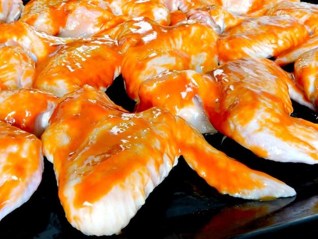 Сырые куриные крылышки в остром красном соусе на противне перед выпечкой.
