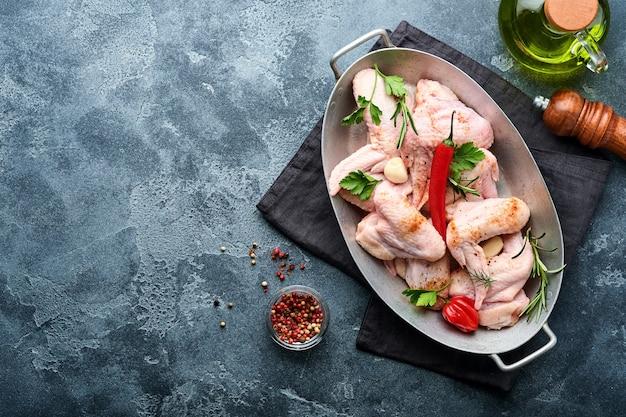 金属製の鍋またはボウルに生の手羽先を入れ、濃い灰色のコンクリート表面で調理するためのスパイスと材料を入れます。黒いテーブルでスパイスと生肉
