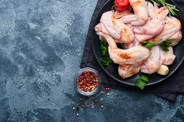 暗い灰色のスレート、石、またはコンクリートの背景で調理するためのスパイスと食材を入れた金属製の鍋またはボウルに入れた生の手羽先。黒いテーブルにスパイスを加えた生肉。上面図。モックアップ。