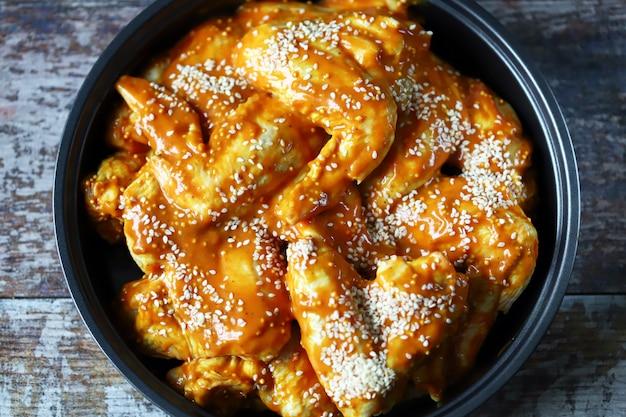 Сырые куриные крылышки, маринованные в сковороде перед приготовлением. готовим куриные крылышки. рецепт крыльев буффало. кето палео. pegan.