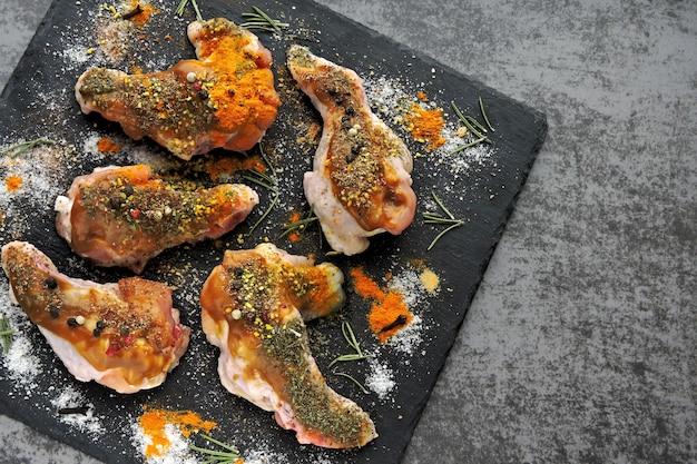 검은 돌 보드에 향신료에 절인 생 닭 날개.