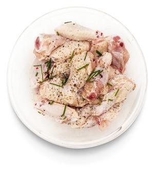 Сырые куриные крылышки, замаринованные с солью, перцем и чесноком в миске, изолированной на белом фоне.