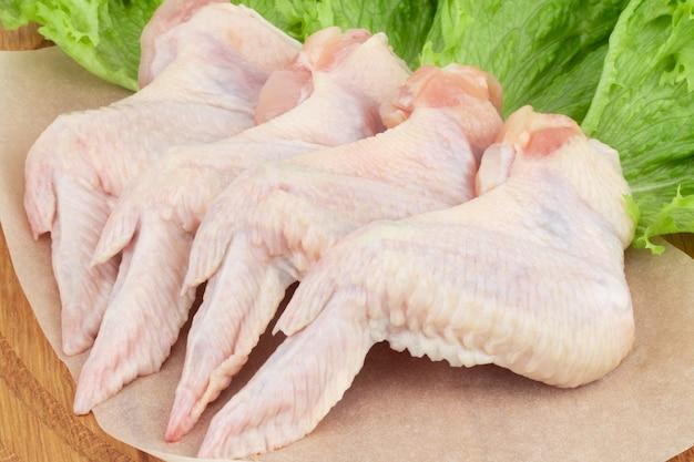 Сырые куриные крылышки на разделочной доске с салатом.