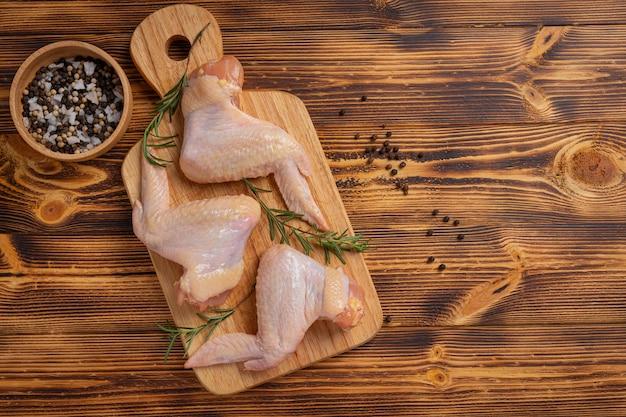 Сырые куриные крылышки на темной деревянной поверхности.