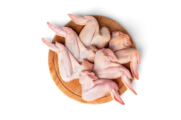 Сырые куриные крылышки на деревянной доске, изолированные на белом фоне.
