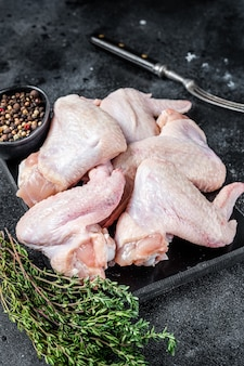 Сырые куриные крылышки мясо птицы на мраморной доске.
