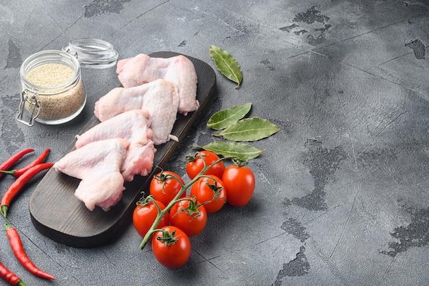 手羽先生鶏肉ハーブセット、ゴマ、木製まな板、灰色の背景、テキスト用のコピースペース