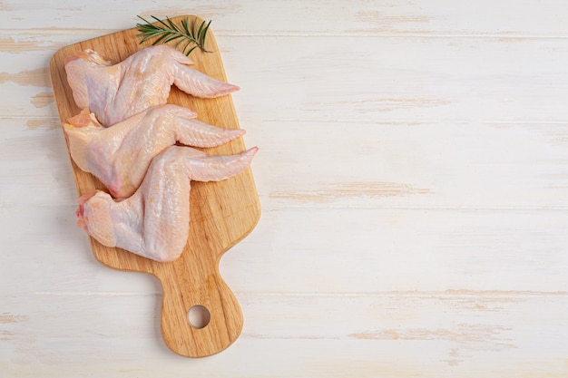 Raw chicken wings on the white wooden surface.