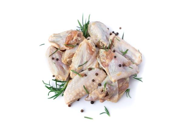 Сырые куриные крылышки с чесноком, перцем и розмарином, изолированные на белом фоне