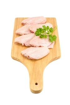 흰색 배경에 고립 된 커팅 보드에 녹색 고수풀과 원시 닭 날개