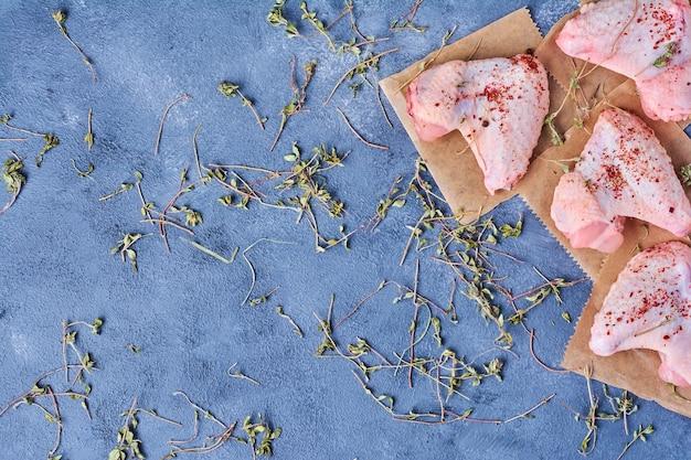 Сырые куриные крылышки с травами и специями на деревянной доске на синем