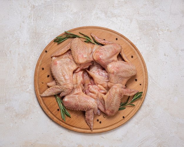 나무 라운드 보드에 로즈마리를 넣은 생 닭 날개. 가정 요리, 편의 식품. 생 가금류 고기