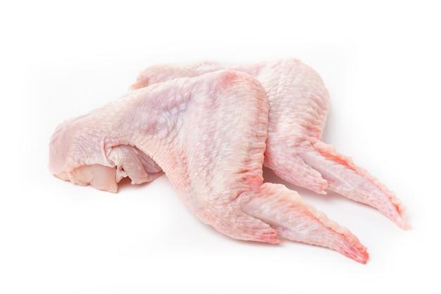 Сырые куриные крылышки с кожей на белом фоне.