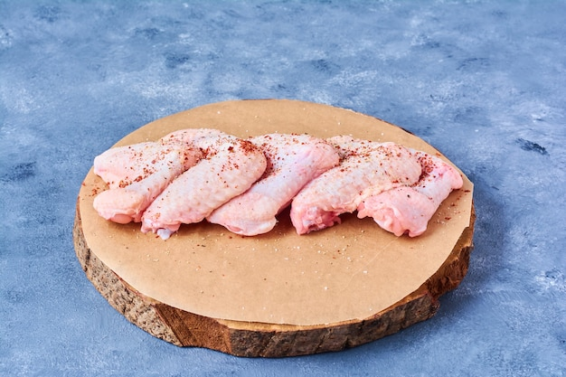 Сырые куриные крылышки со специями на деревянной доске на синем