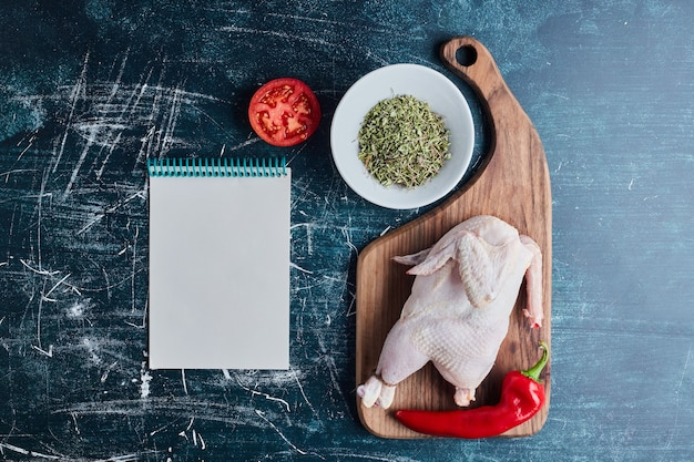 Raw chicken with herbs and spices and a recipe book aside.