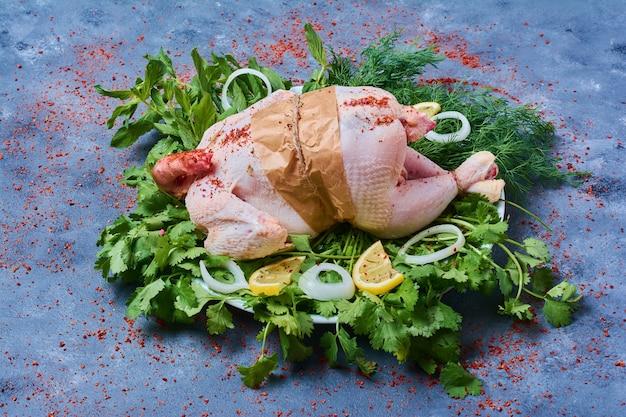 Pollo crudo con erbe su una tavola di legno sull'azzurro