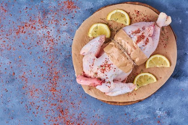 Сырая курица с лимоном на деревянной доске на синем