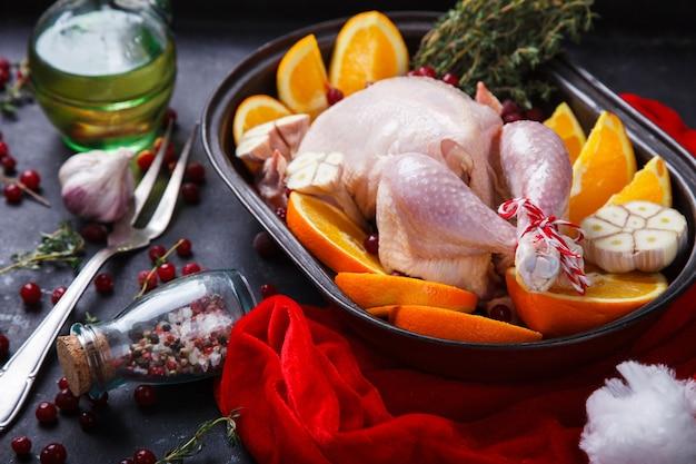 Сырая курица с апельсинами и клюквой на рождество.