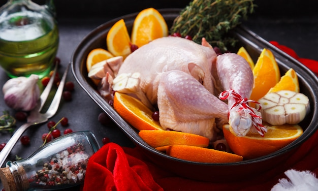 Raw chicken with oranges and cranberries for christmas. thanksgiving dinner. selective focus.