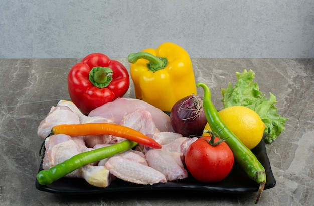 ダークプレートに野菜と生の鶏肉。高品質の写真