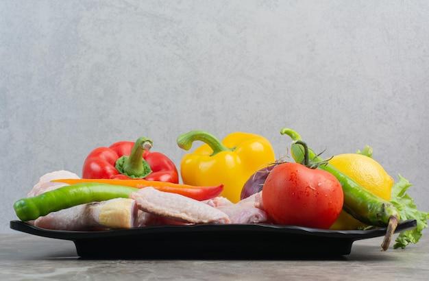 Сырая курица с овощами на темной тарелке. фото высокого качества