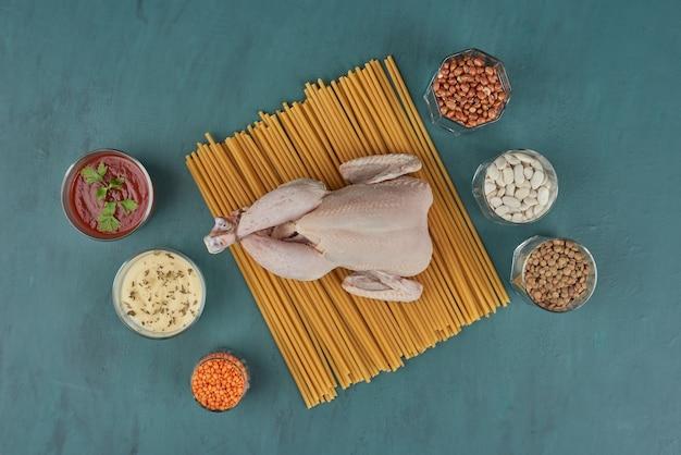 Pollo crudo su una tavola di legno con fagioli e spezie, vista dall'alto.