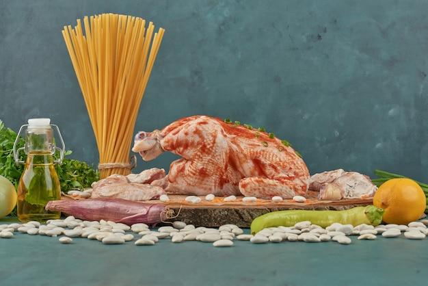 Pollo crudo su una tavola di legno con spezie e pasta.