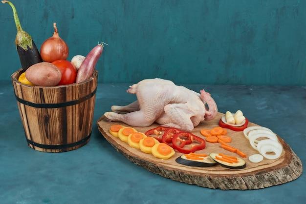 Pollo crudo su una tavola di legno con verdure nel secchio.