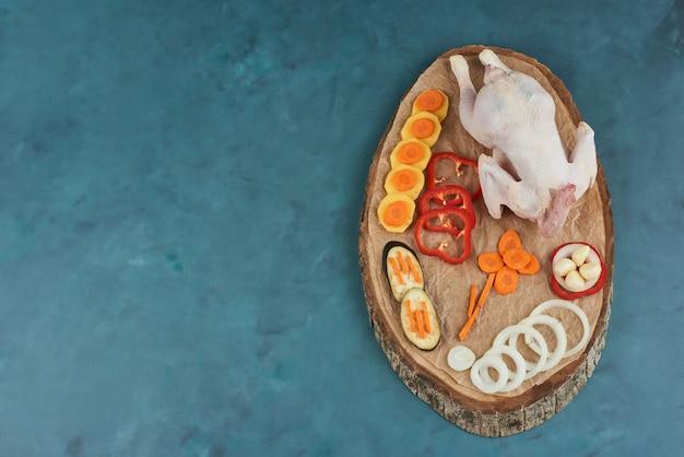 Pollo crudo su una tavola di legno con verdure.