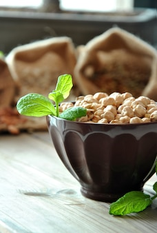 Raw chickpeas in a brown bowl with herbs