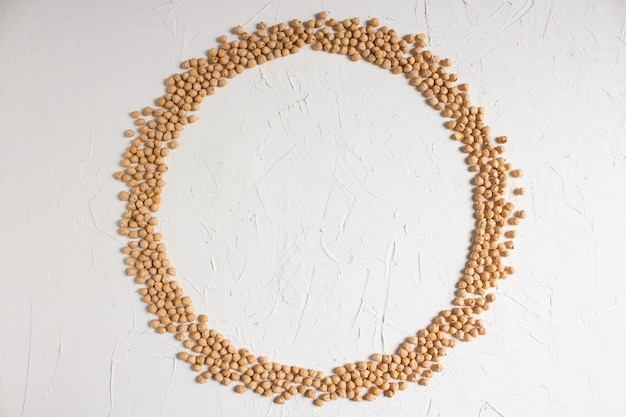 Raw chickpeas, round frame of chickpeas on a light background