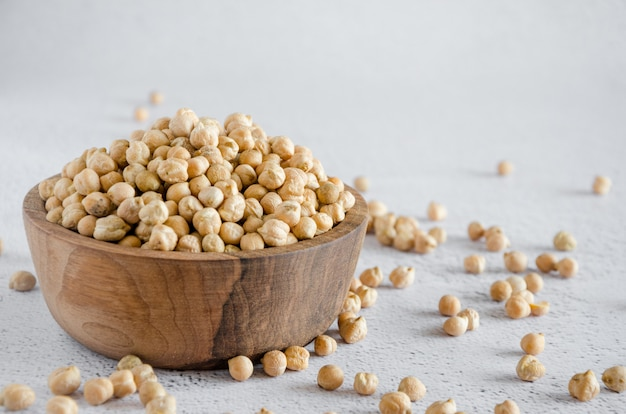 Raw chickpeas on a wooden bowl on a light surface. chickpeas is nutritious food. healthy and vegetarian food. horizontal, copy space.